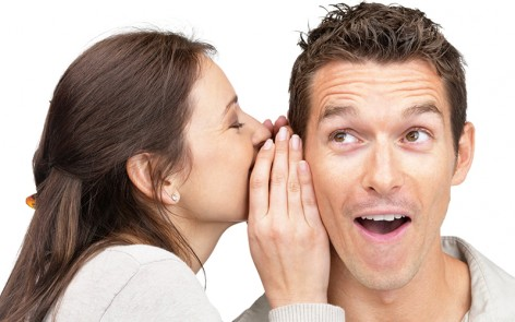 Woman whispering in a man's ear